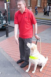 Vision impaired man and guide dog prepare to cross a road