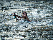 19 JUNE 2016 - DON KHONE, CHAMPASAK, LAOS: A fisherman uses a hand over hand rope bridge to get across the Mekong River at Khon Pa Soi Waterfalls, on the east side of Don Khon. It's the smaller of the two waterfalls in Don Khon. Fishermen have constructed an elaborate system of rope bridges over the falls they use to get to the fish traps they set. Fishermen in the area are contending with lower yields and smaller fish, threatening their way of life. The Mekong River is one of the most biodiverse and productive rivers on Earth. It is a global hotspot for freshwater fishes: over 1,000 species have been recorded there, second only to the Amazon. The Mekong River is also the most productive inland fishery in the world. The total harvest of fish from the Mekong is approximately 2.5 million metric tons per year. By some estimates the harvest in the Tonle Sap (in Cambodia) had doubled from 1940 to 1995, but the number of people fishing the in the lake has quadrupled, so the harvest per person is cut in half. There is evidence of over fishing in the Mekong - populations of large fish have shrunk and fishermen are bringing in smaller and smaller fish.     PHOTO BY JACK KURTZ