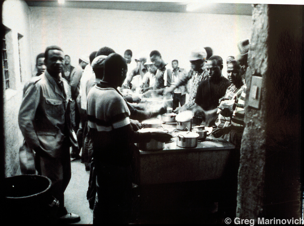 Migrant workers prpare supper in Mamelodi hostel, Mamelodi, Pretortia, 1989. Scanned from original polaroid.