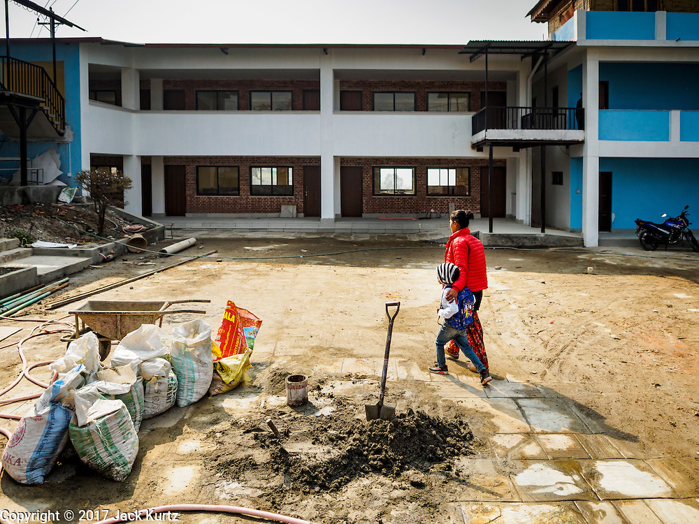 01 MARCH 2017 - KHOKANA, NEPAL: A woman and her daughter walk into a new school in Khokana. The school, one of the few signs of earthquake recovery, was built after the 2015 earthquake destroyed the original school. Recovery seems to have barely begun nearly two years after the earthquake of 25 April 2015 that devastated Nepal. In some villages in the Kathmandu valley workers are working by hand to remove ruble and dig out destroyed buildings. About 9,000 people were killed and another 22,000 injured by the earthquake. The epicenter of the earthquake was east of the Gorka district.     PHOTO BY JACK KURTZ