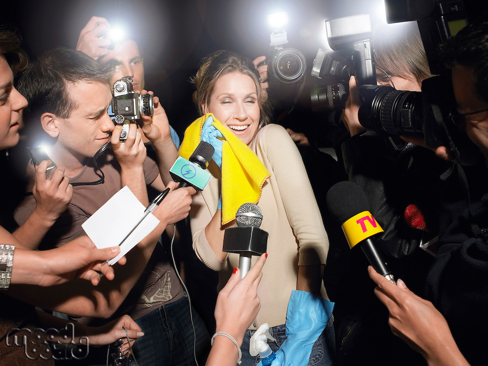 Woman with cleaning equipment surrounded by paparazzi