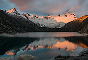 In golden light of sunset, Nevado Santa Cruz Norte (5829 m or 19,120 ft) reflects in Lake Cullicocha (4628 m or 15,174 ft). This was day 8 and camp 8 of 10 days trekking around Alpamayo in Huascaran National Park (UNESCO World Heritage Site), Cordillera Blanca, Andes Mountains, Peru, South America.