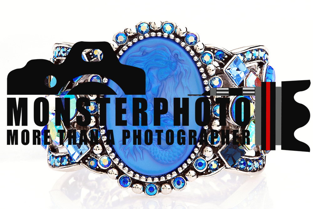 this antiqued silvertone Sirens Song mermaid cuff bracelet features different shapes and colors of crystals accenting an open work design. The center of the_________ cuff features a large oval purple/blue moonstone mermaid, framed with alternating round crystals and beaded accent. Hinged closure. Fits an average size wrist.
