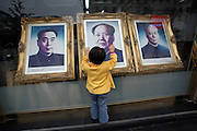 A girl looks at a portraits of Chinese Chairman Mao Zedong (C) and other historial communist leaders in a shop in Beijing's Wangfujing shopping street in central Beijing May 25, 2006.