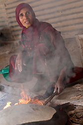 Middle East, Israel, Laqiya, Bedouin woman baking flatbread over fire.  MR
