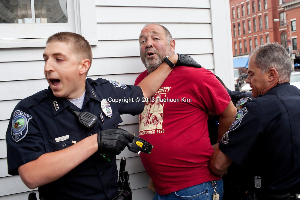 Daniel Musso, of Brentwood, is apprehended by law enforcement officers during a gun control rally supported by Mayors Against Illegal Guns in Concord on Tuesday, June 18, 2013.