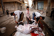 A butcher slaughters a cow on a street in the city center of embattled Deir az-Zor. Residents of eastern syrian town Deir az-Zor joined arab spring protests against the regime of Bashar al-Assad from its early beginning in March 2011. Since summer 2012 the town with few hundred thousand inhabitants is embattled between the Syrian Army and different opposing rebel groups like Free Syrian Army and Jabhat al-Nusra. Deir az-Zor is target to constant shelling by artillery, war planes and short range missiles. Almost 70 percent of the town is rebel held while government forces remain in control over some residental areas and a strategic important airport. Deir az-Zor is widely damaged and some areas almost totally destroyed by fierce and long lasting battles. All direct road connections to Deir az-Zor are cut and fighters and returning residents as well depend on one provisional supply line across the Euphrates river which is regularly targeted by government snipers.