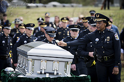 April 4, 2017 - Louisville, Kentucky, U.S. - Officers lay flowers on the casket of Louisville Metro Police Officer Nick Rodman following his funeral in Louisville, Kentucky, Sunday, April 4, 2017.  Officer Rodman was killed in the line of duty last week during a vehicle pursuit. (Credit Image: © Bryan Woolston via ZUMA Wire)
