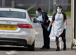 © Licensed to London News Pictures. 28/03/2020. Chessington, UK. A nurse talks to a driver before taking a swab at a newly opened drive through virus testing centre for NHS staff in the car park of Chessington World of Adventures. Death rates from the spread of coronavirus continue to climb. Both the Prime Minister Boris Johnson and Health Secretary Matt Hancock have tested positive for the virus and are now self isolating. Photo credit: Peter Macdiarmid/LNP