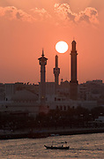 Dubai Creek. Water taxis, sunset behind the minarets of the Grand Mosque in Bur Dubai.