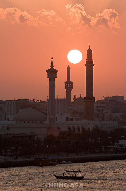 Dubai Creek. Water taxis, sunset behind the minarets of the Grand Mosque in Bur Dubai.