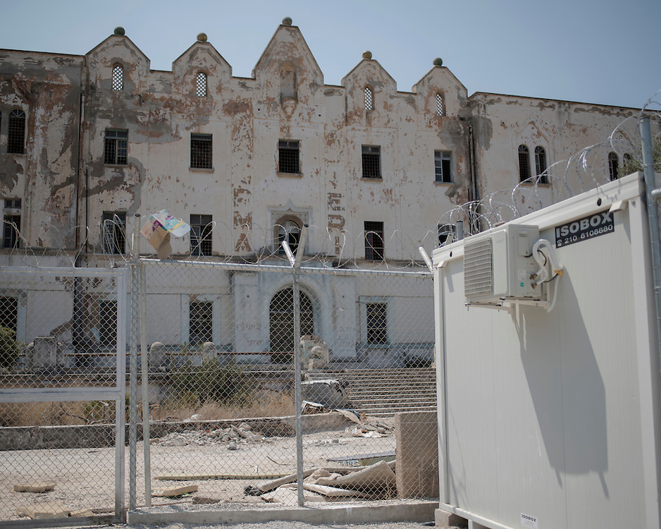 The remains of the abandoned Lepida psychiatric hospital, in whose grounds the Leros &lsquo;Hot spot&rsquo; (an EU-run migrant&rsquo;s reception centre) has been built. <br /> <br /> The Hot Spot in Lepida opened on the 26th of February 2016 in the grounds of the former Lepida psychiatric hospital.  At the beginning it served as a registration camp for refugees and migrants who were travelling to Europe through Greece but since the closure of the borders in March 2016 it serves as a permanent camp. People are allowed to go out, they have three meals a day, the prefabricated huts have a bathroom and are air-conditioned and compering to other refugee camps in Greece the conditions are bearable.