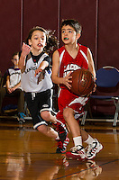 Sanbornton's Sam Mattes and Laconia's Carson Tucker on the court during the 9am junior division championship game of the 22nd annual Francoeur Basketball Tournament Sunday morning at Gilford Middle School.  (Karen Bobotas/for the Laconia Daily Sun)