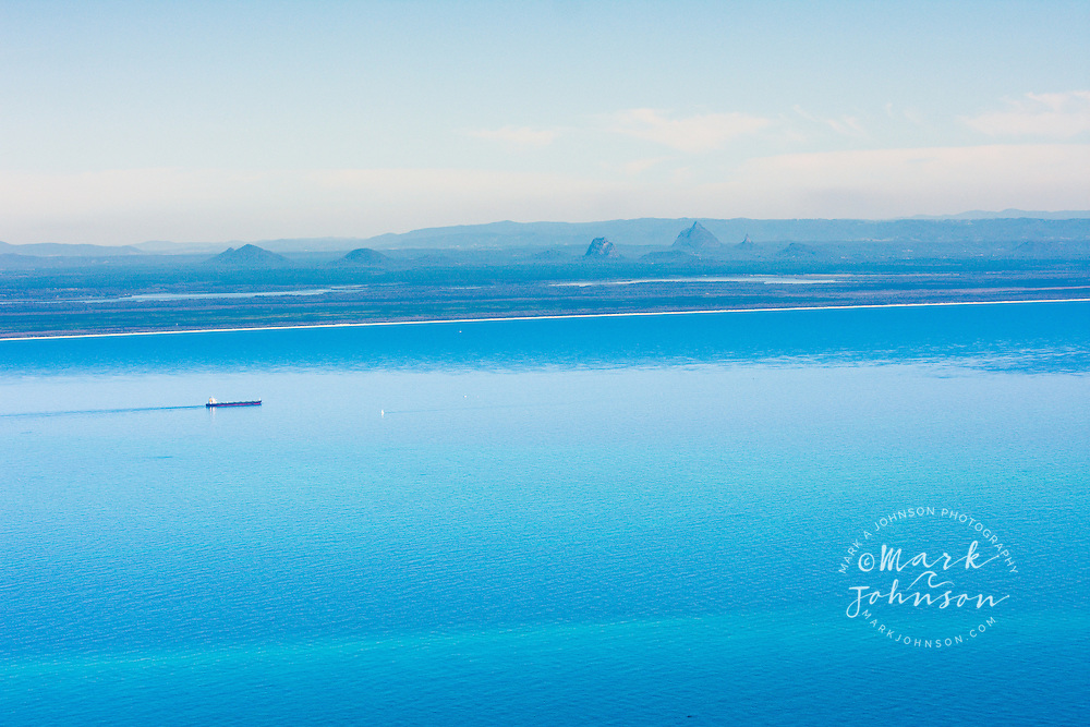 Aerial photograph of a cargo ship on super calm Moreton Bay with the Glasshouse Mountains in the background, Queensland, Australia