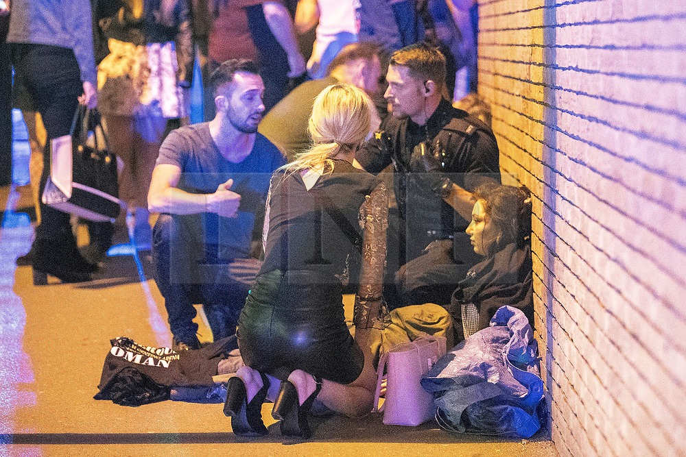 © Licensed to London News Pictures . FILE PICTURE DATED 23/05/2017 as Manchester prepares to mark a year since the Manchester Arena terror attack . Manchester, UK. Georgina Foulk (facing away) and fiancé James Smith (left) treating a girl on the pavement . Police and other emergency services are seen near the Manchester Arena after Salman Abedi murdered 22 and injured dozens more at an Ariana Grande concert at Manchester Arena. Photo credit: Joel Goodman/LNP