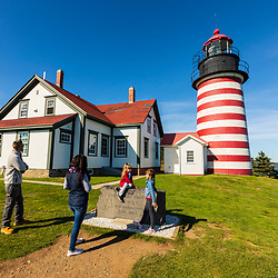 A family eplores outside the West Quoddy Head Lighthouse in Lubec, Maine. Easternmost point in the United States.