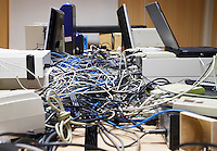 Mess of wires connecting computers and printers in office