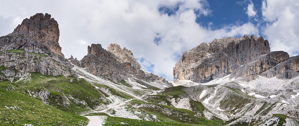 Hike the Vajolet/Vaiolet valley towards Passo Principe and Catinaccio d'Antermoia/Kesselkogel (right, 9849 feet/3002m), highest peak in the Rosengarten/Catinaccio Dolomites, Italy, Europe. From Pera di Fassa village (in Pozza di Fassa comune in Val di Fassa), in Trentino-Alto Adige/Südtirol region, Italy, take a bus or lift to visit Rifugio Gardeccia Hutte and hike upwards. 200 million years ago, Triassic coral reefs fossilized into Dolomite. Collision of tectonic plates lifted the Dolomites within the Southern Limestone Alps. UNESCO honored the Dolomites as a natural World Heritage Site in 2009. This panorama was stitched from 3 overlapping photos.