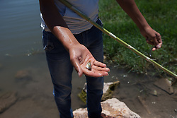 Syria.<br /> A syrian resident of Al-Qala shows to the photographer camera a small fish alive in a small lake  in the town of Al-Qala a small town with an ancient castle occupied by the Syrian regime in Hama province, Syria,<br /> 15th June 2013<br /> Picture by Daniel Leal-Olivas / i-Images