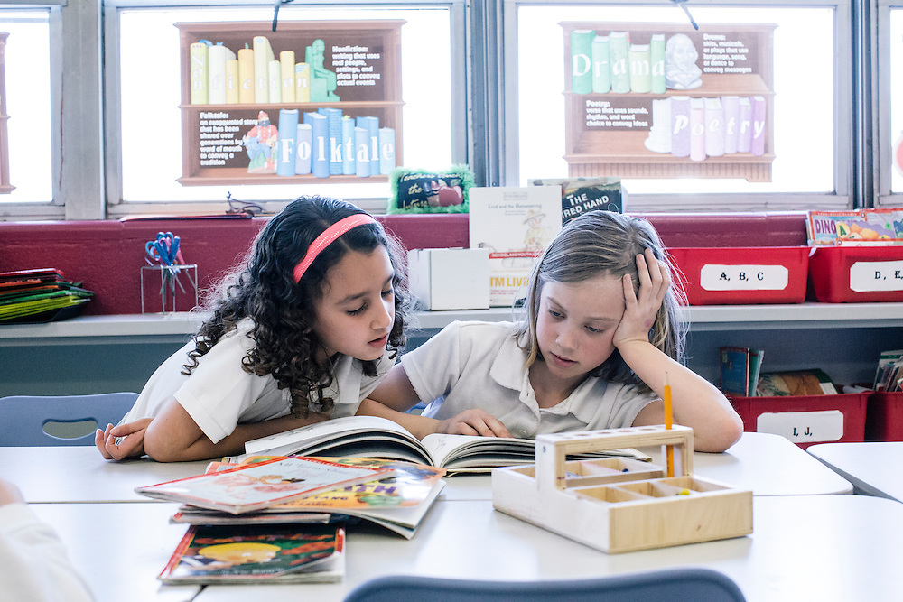 Yarelis Cortes, 7, left, and Mya Thurston, 7, both of which have parents in the military, read together during class at Leckie Elementary School in SW Washington, D.C. Nearly a third of the school is attended by the children of military families.