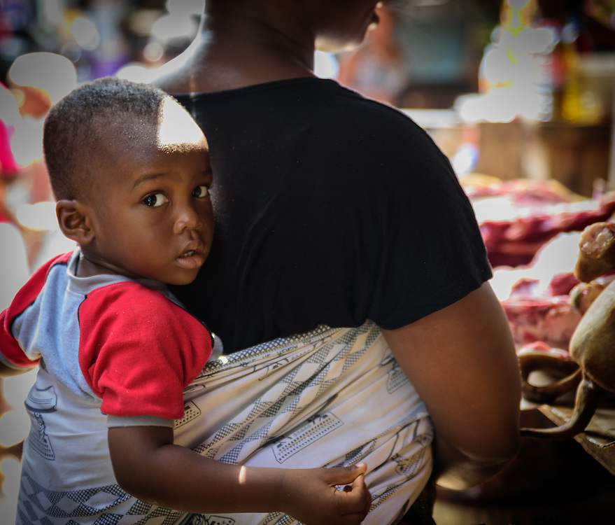 Small boy in jeans being carried on the back of a woman, Ghana.