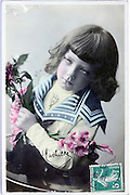 hand colored in studio photo postcard of a child holding flowers