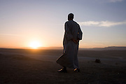 A local Egyptian businessman looks thoughtfully into a setting sun while on sand dunes of a desert enviroment, near a village on the West Bank of Luxor, Nile Valley, Egypt. Hamdy Mosa has worked in the tourism industry all of his adult life and now heads a family business dependent on the industry, currently enduring a downturn in visitor numbers after recent terrorist activity.