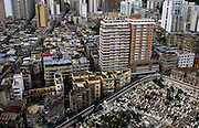 An aerial view of Central Macau, looking down on the ex-Portuguese colony including its Chinese Christian cemetery of San Miguel. Macau is now administered by China as a Special Economic Region (SER). Taken from a tall apartment block that overloooks the Rua do Almirant e Costa Cabral, we can view the tightly-packed cities of one of the most densely-populated connurbations in the world, this area is a packed warren of houses, businesses and tower blocks, home to a population of mainland 95% Chinese, primarily Cantonese, Fujianese as well as some Hakka, Shanghainese and overseas Chinese immigrants from Southeast Asia and elsewhere. The remainder are of Portuguese or mixed Chinese-Portuguese ancestry, the so-called Macanese, as well as several thousand Filipino and Thai nationals. The official languages are Portuguese and Chinese. The Macau Special Administrative Region, more commonly known as Macau or Macao is one of the two special administrative regions (SARs) of the People's Republic of China (PRC), along with Hong Kong. Administered by Portugal until 1999, it was the oldest European colony in China, dating back to the 16th century. The administrative power over Macau was transferred to the People's Republic of China (PRC) in 1999, 2 years after Hong Kong's own handover. Macao's gambling revenue in 2006 weighed in at a massive £3.6bn - about £100m more than Las Vegas.
