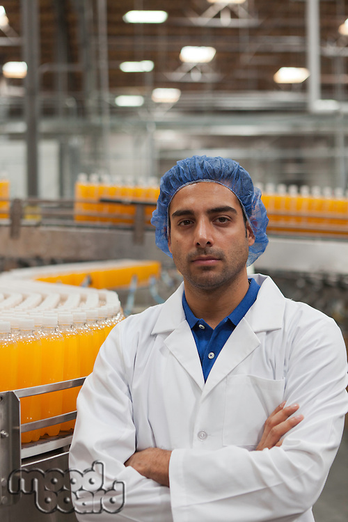 Portrait of factory worker standing with arms crossed at bottling plant