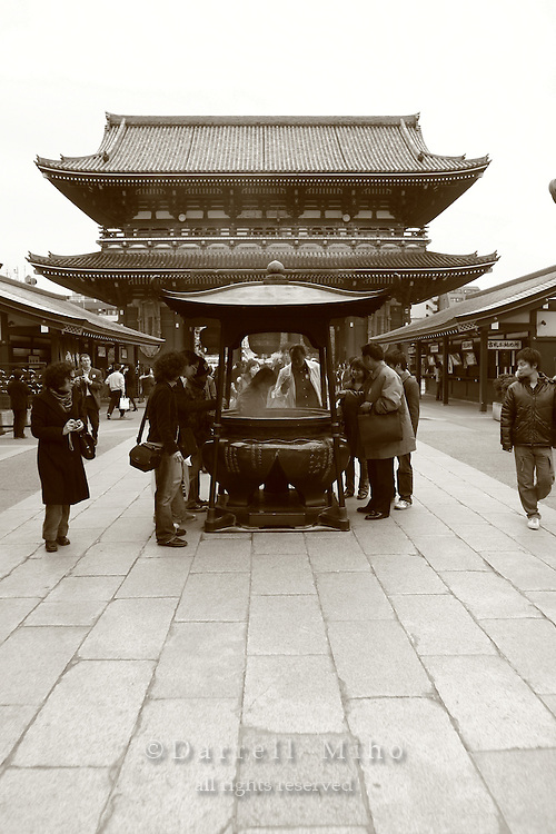 Mar 6, 2006; Tokyo, JPN; Asakusa.Visitors gather around a large bronze incense bowl outside the Senso-ji Buddhist temple (not pictured)and waft the smoke (considered to be the breath of the gods) upon themselves for its supposed curative powers...The Hozo-mon (treasure gate) can be seen in the background...Photo credit:  Darrell Miho