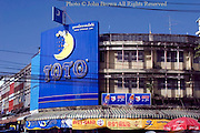 A large blue sign marks the location of a Toto Bed Store on a city street in Chiang Rai, Thailand.