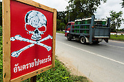 08 JULY 2013 - MAYO, PATTANI, THAILAND:  A sign on the side of a highway in Pattani province of Thailand warning motorists of IEDs on the road. The signs have been showing up on highways in Pattani and Yala provinces. No one has taken credit for the signs and the Thai government doesn't know who is putting them up. Eight Thai soldiers were injured - one seriouly and seven with minor injuries - when their truck was hit by an IED just a few kilometers from this sign, outside Mayo, Pattani province in southern Thailand Monday. The soldiers were returning from a teacher protection mission when their truck ran over the explosive. The attack was thought to be conducted by Muslim insurgents who have been battling the Thai government for greater autonomy. The conflict in southern Thailand has claimed about 5,000 lives since 2004.   PHOTO BY JACK KURTZ