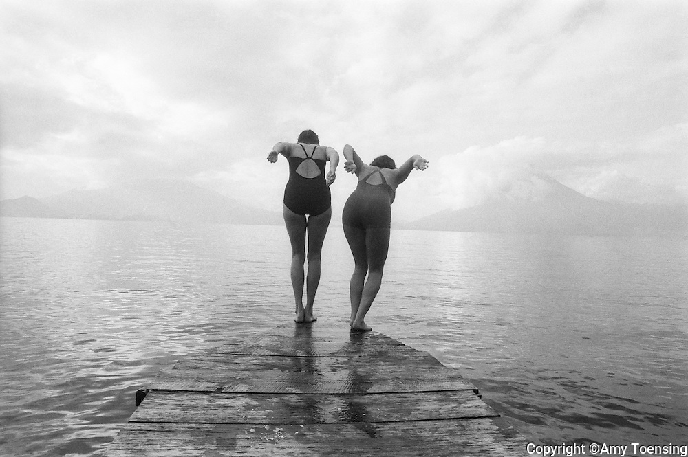 LAKE ATITLAN, GUATEMALA -- JANUARY 01, 1996-- Two women dive in for a morning swim January 01, 1996 in Lake Atitlan, Guatemala. (Photo by Amy Toensing/Getty Images) _________________________________<br /> <br /> For stock or print inquires, please email us at studio@moyer-toensing.com.