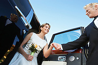 Man helping young woman from limousine