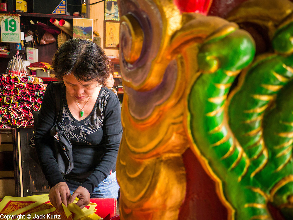 20 DECEMBER 2012 - KUALA LUMPUR, MALAYSIA:  People prepare offerings at the Guan Di Temple in Kuala Lumpur, Malaysia. Guan Di Temple (God of War Temple) was built in 1888 and is one of the oldest Chinese Temples in Kuala Lumpur.  PHOTO BY JACK KURTZ
