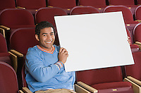 Man sitting in auditorium, holding empty placard