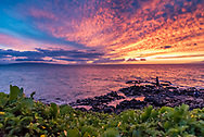 A boy fishes in the ocean at sunset near Kamaole Beach Park II in Kihei, Maui.
