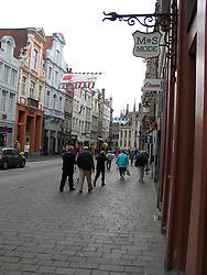 Shops along cobbled sidewalk, Bruges, West Flanders, Belgium