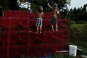 Morgan Serigne, 6, with his brother Logan Serigne, 4, playing on empty crab pots near their home in St Bernard, LA on July 20, 2010. The crab pots were pulled onto land after the waters were closed to crab fishing after the Deepwater Horizon Oil Spill.