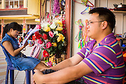 12 MARCH 2013 - ALONG HIGHWAY 13, LAOS: A couple that owns a shop in the Chinese market in Oudomaxy waits for customers. The Chinese market in Oudomaxy is still under construction but much of the market is empty. Oudomaxy has a large Chinese immigrant community. By some estimates, as much as 40% of the people now living in the town are originally from China, most from the province Yunnan in southern China. The paving of Highway 13 from Vientiane to near the Chinese border has changed the way of life in rural Laos. Villagers near Luang Prabang used to have to take unreliable boats that took three hours round trip to get from the homes to the tourist center of Luang Prabang, now they take a 40 minute round trip bus ride. North of Luang Prabang, paving the highway has been an opportunity for China to use Laos as a transshipping point. Chinese merchandise now goes through Laos to Thailand where it's put on Thai trains and taken to the deep water port east of Bangkok. The Chinese have also expanded their economic empire into Laos. Chinese hotels and businesses are common in northern Laos and in some cities, like Oudomxay, are now up to 40% percent. As the roads are paved, more people move away from their traditional homes in the mountains of Laos and crowd the side of the road living off tourists' and truck drivers.    PHOTO BY JACK KURTZ