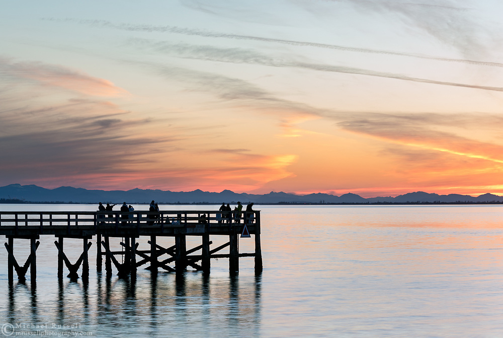 Tourists and locals watching the sunset from the pier at Crescent Beach in Surrey, British Columbia, Canada. The mountains in the background beyond Boundary Bay are on Vancouver Island.