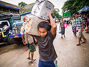 13 JUNE 2013 - YANGON, MYANMAR:   A man carries boxes to a boat at the Aung Mingalar Jetty in Yangon. The jetty is a stop for commuters who live on the far side of the Irrawaddy River and ride small boats back and forth across the river. Yangon, formerly Rangoon, is Myanmar's commercial capital and used to be the national capital. The city is on the Irrawaddy River and has a vibrant riverfront.  PHOTO BY JACK KURTZ