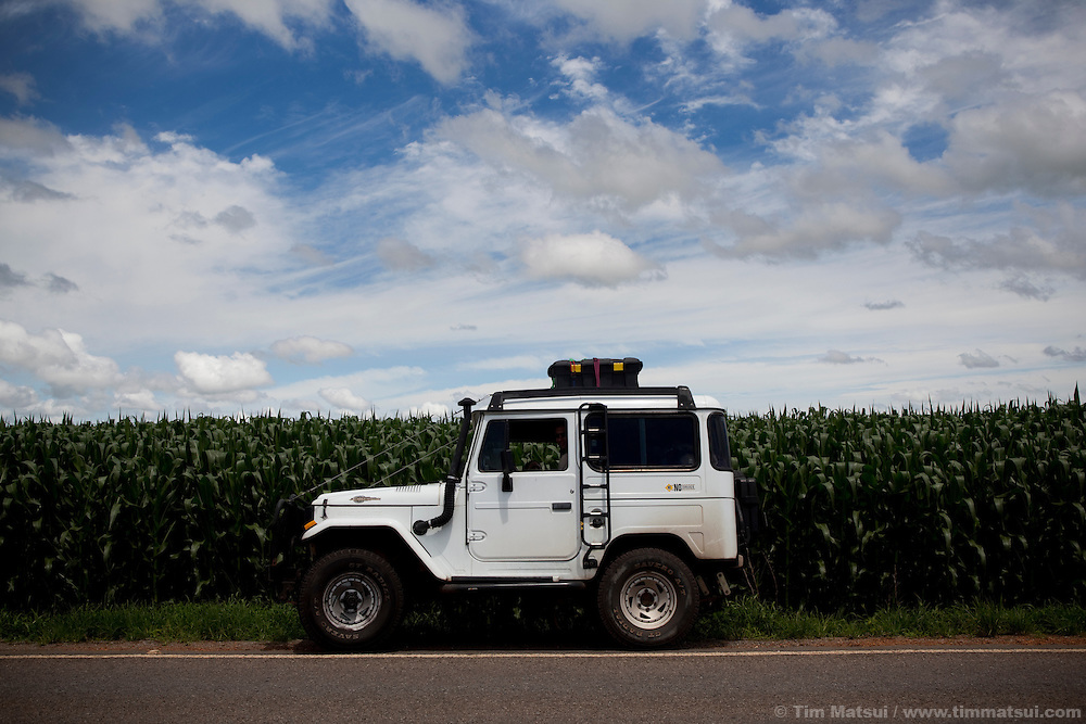 A land cruiser jeep parked at the side of the road and a corn field.