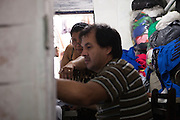 Rosmery and her husband sewing in their home in São Paulo, Brazil, where they live with their seven children and their grandson.<br /> <br /> Rosmery and her husband are Bolivian and moved to Brazil in search of work. Prior to moving in to their own home they lived and worked in a sewing workshop with their family, often for up to 16 hours a day. <br /> <br /> Nowadays they still sew and have long days, but they are based from home.<br /> <br /> They have have received a lot of help and support from Missao Paz who work in partnership with C&A Foundation to  offer advice and support on employment, health, family, community and education. <br /> <br /> Their mission is to welcome, understand, integrate and celebrate the lives of immigrants and refugees, dreaming of a universal citizenship.