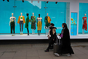 Muslim lady shoppers walk past a Debenhams department store window on Oxford Street, on 4th March 2019, in London England.