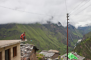 A man perches on the roof of a building in the Subhai village, Uttarakhand, Central Himalayas, India.