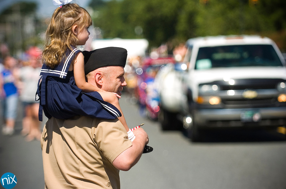 Philip Elmore, and his daughter Isabella, 3, watch during Harrisburg's July 4th parade Saturday morning..