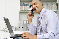 Businessman using laptop and mobile phone at desk portrait