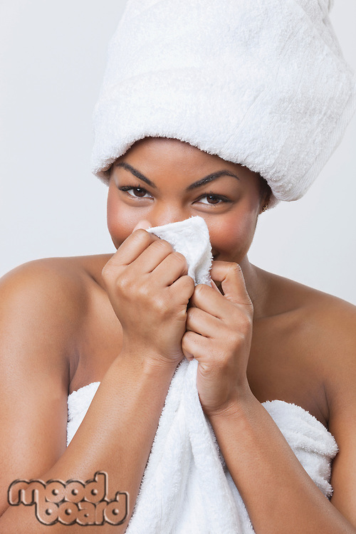 Portrait of smiling young African American woman wrapped in towel over white background