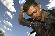 A man who crossed illegally from Mexico in to the U.S. douses himself with water along a trail on the Buenos Aires National Wildlife Refuge in the Sonoran Desert in temperatures exceeding 100 degrees north of Sasabe, Arizona, USA.